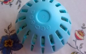 a blue plastic sphere looking like and egg with small round laundry washing beads inside