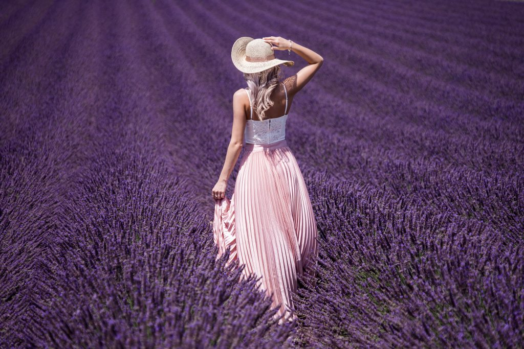 a woman in white pink dress and summer hat walks through field of lavender. You can see her back only.