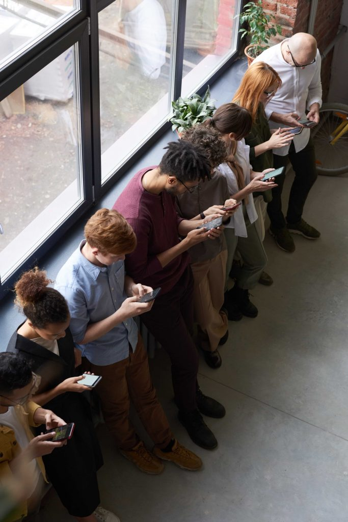 row of young people each staring at their mobile phone