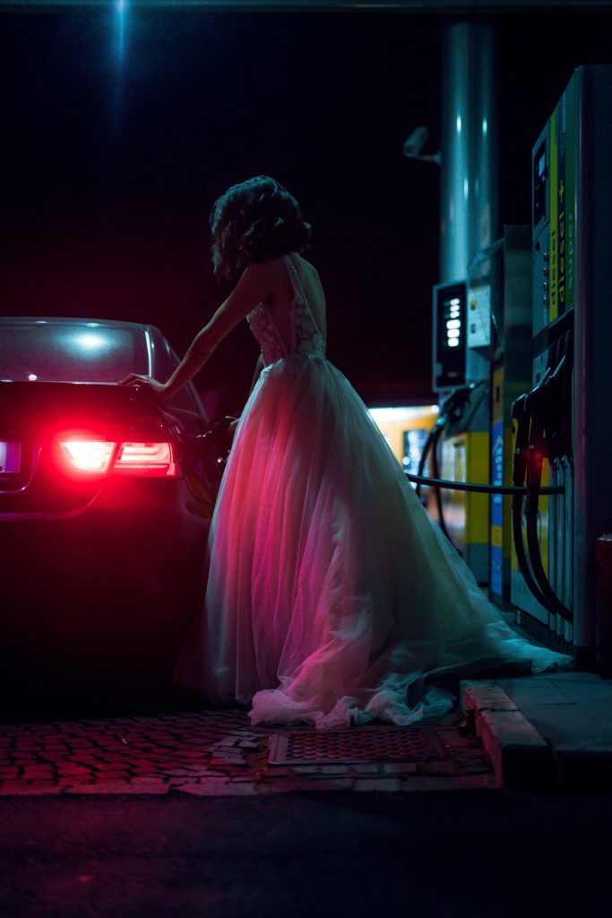 a woman in white evening dress at night fueling the car