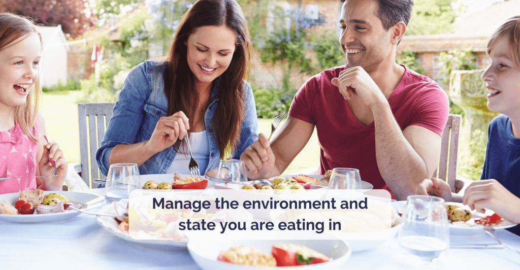 a happy young smiling family sitting at set table with fresh healthy food and garden in a background. Caption ' 'Manage the environment you are eating in.'