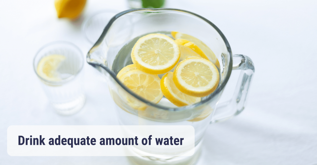 a large glass pitcher of water and lemon slices with glass full of water and lemon slice next to it. Caption ' Drink adequate amount of water'