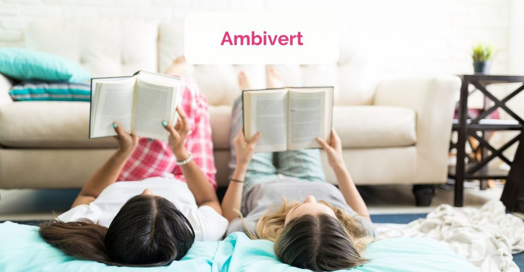two teens lying on their back on the floor with legs up on the sofa, reading books, caption ' Ambivert'