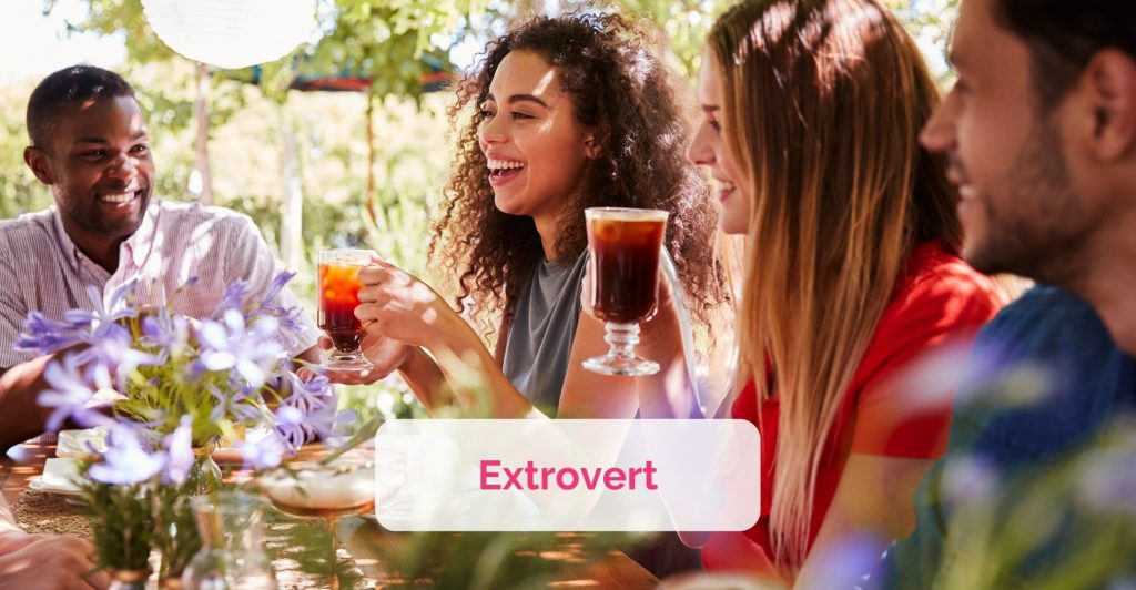 Grounp of young adults sitting at the table outdoors, table covered with foods and drinks, two women holding colourful drink in their hand laughing. Caption ' Extrovert'