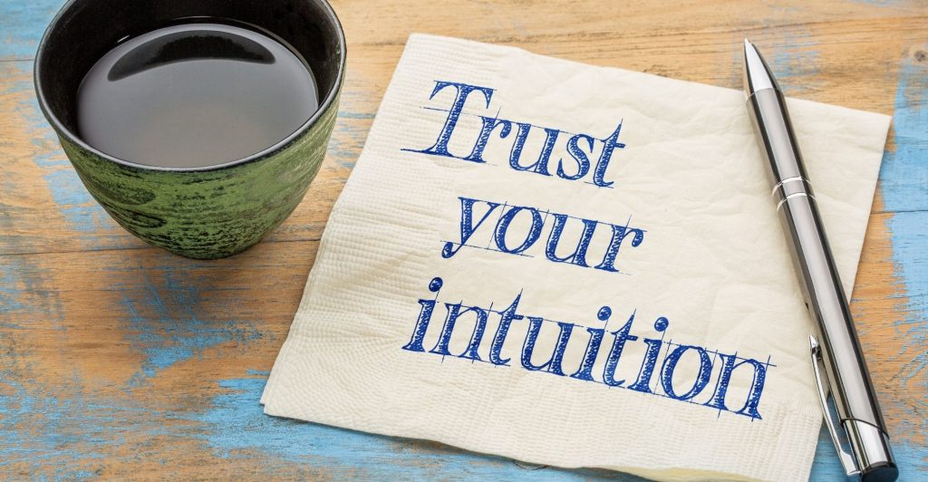 cup full of coffee and note next to it saying 'Trust Your Intuition'